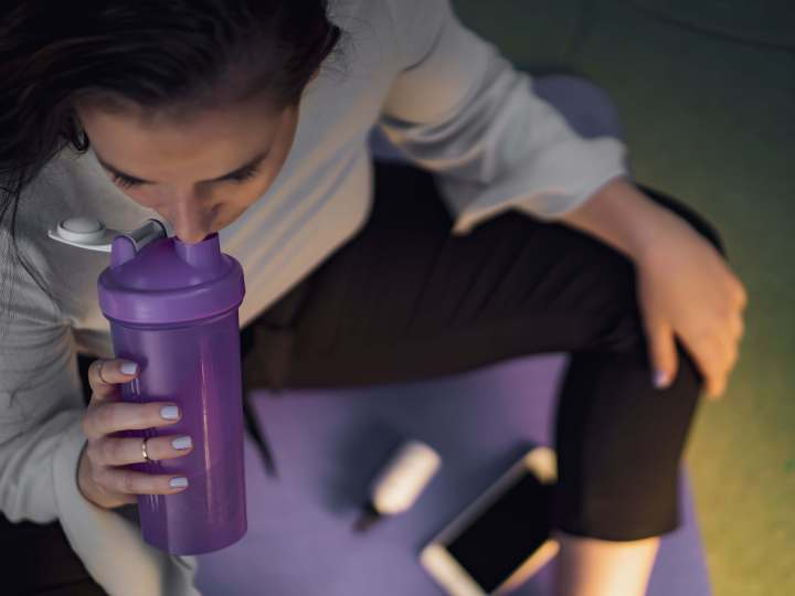 Woman sipping from a gym shaker